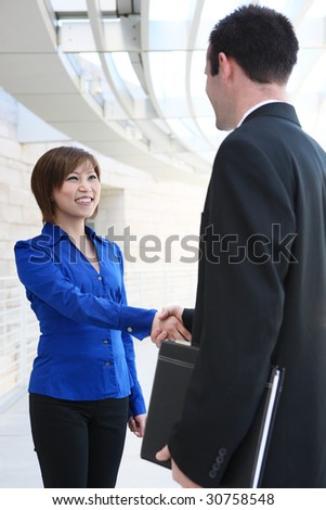 An attractive diverse business team shaking hands at office building