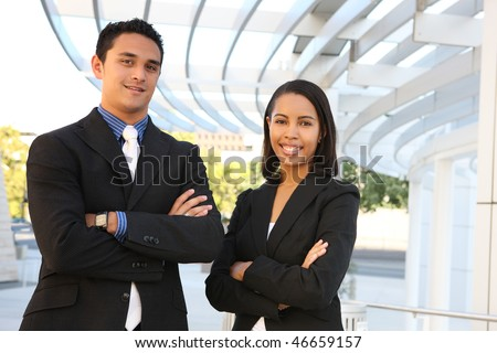 An attractive, diverse man and woman business team at their company office building