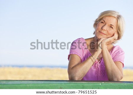 An attractive elegant and happy senior woman sitting outside out a table and thinking, behind her is a beach and the sea