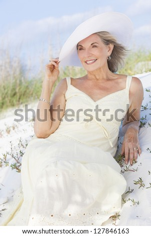 An attractive elegant classy senior woman in a yellow sun dress & white sun hat sitting on a white sand beach with grass and a blue sky behind her.