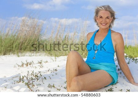 An attractive elegant senior woman in a blue swimming costume sitting on a white sand beach with grass and a blue sky behind her.
