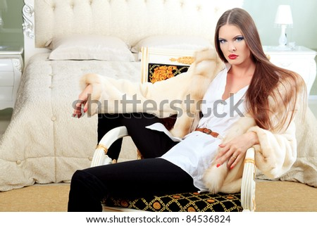 An attractive fashionable woman posing in the interior.