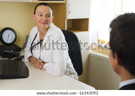 An attractive female doctor listening to a male patient, with a blood pressure monitor beside her