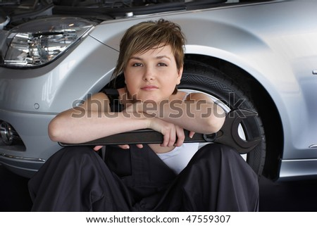 An attractive, friendly auto mechanic sitting with spanner wrench near the car - stock photo