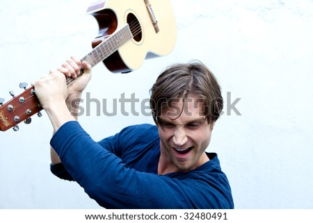 An attractive guitar player with a blue shirt and white background