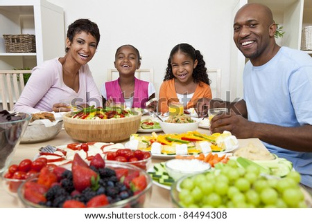 An attractive happy African American, smiling family of mother, father, two daughters eating salad and healthy food at a dining table. - stock photo
