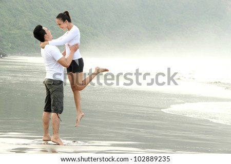 An attractive happy couple having fun on the beach