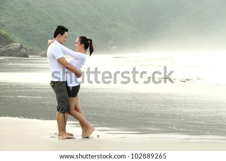 An attractive happy couple hugging on the beach