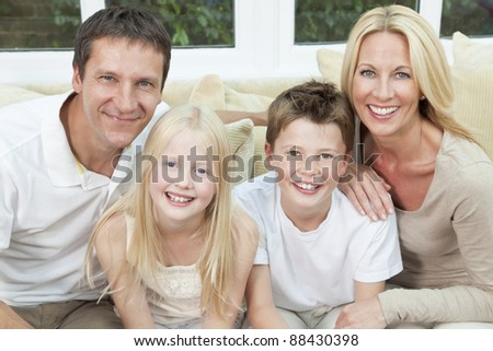 An attractive happy family of mother, father, son and daughter sitting on a sofa at home having fun - stock photo