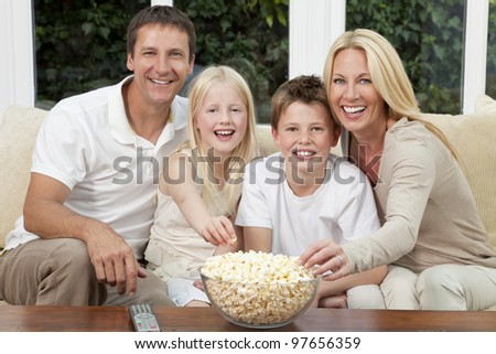 An attractive happy family of mother, father, son and daughter sitting on a sofa at home watching a film or television and eating popcorn.