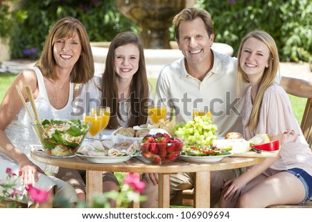 An attractive happy, smiling family of mother, father and two daughters eating healthy food at a table outside.