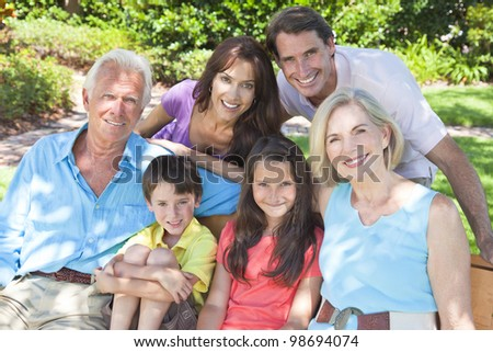 An attractive happy, smiling family of mother, father, grandparents, son and daughter sitting on a bench outside in the sunshine.