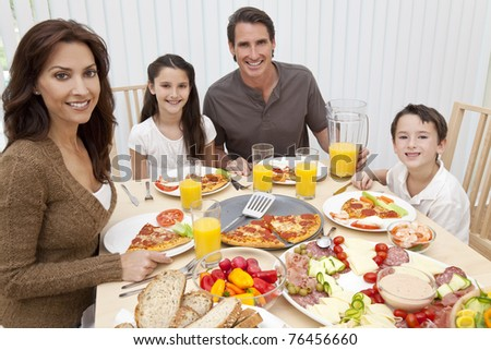 An attractive happy, smiling family of mother, father, son and daughter eating salad and pizza at a dining table.