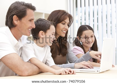 An attractive happy, smiling family of mother, father, son and daughter sitting at a table using a white laptop computer