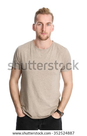 An attractive healthy man standing against a white background wearing a beige t-shirt. Stock fotó ©