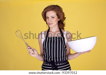 An attractive housewife is preparing a mixture for baking. Beautiful housewife. Beautiful housewife.