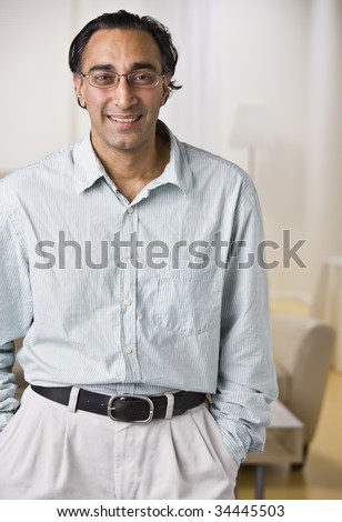 An attractive Indian man posing.  He is dressed in business attire and is smiling at the camera.  Vertically framed shot.