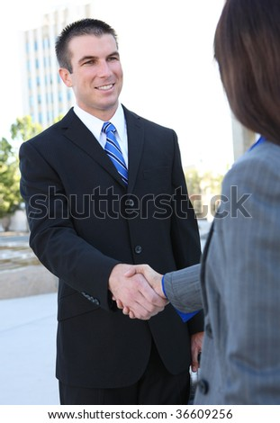 An attractive man and woman business team shaking hands at office building