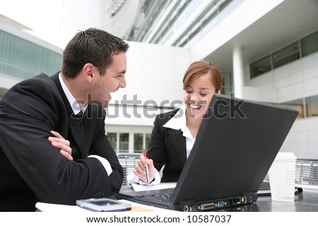 An attractive man and woman business team working on computer