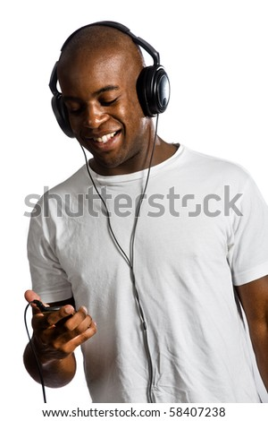 An attractive man listening to music on his headphones against white background