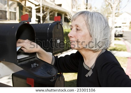 An attractive mature woman checking her mailbox