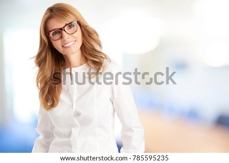 An attractive mature woman standing inside and smiling to the camera. #785595235