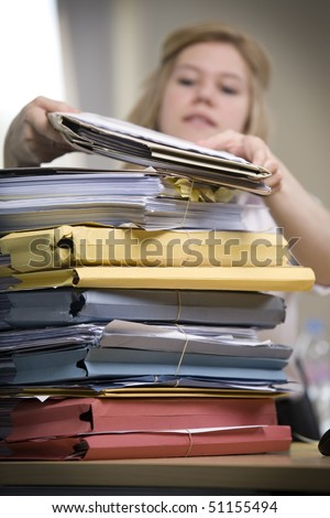 An attractive office worker slowly gets through a large stack of files.