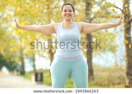 An attractive plus size woman in a sports top and leggings, goes in for sports, works out in a cozy city park. High quality photo. ストックフォト ©