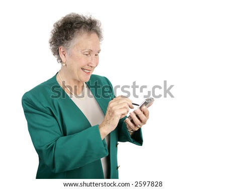 An attractive senior businesswoman having fun with her new palm pilot.  Isolated on white with room for text. - stock photo