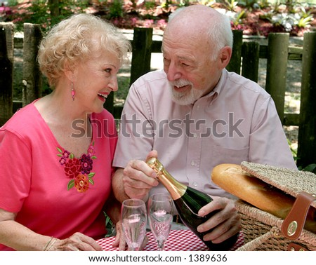 An attractive senior couple on a picnic, looking lovingly into each-others eyes as he opens the wine.