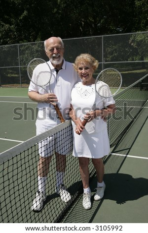 An attractive senior couple on the tennis courts.  Full view vertical.