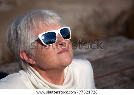 An attractive senior woman sits with her head back, soaking in the rays of the sun.