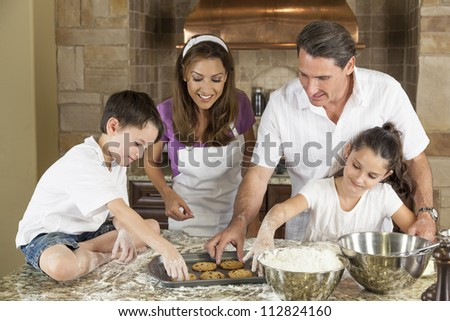 An attractive smiling family of mother, father, and two children baking and eating fresh chocolate chip cookies in a kitchen at home