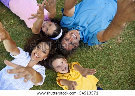 An attractive smiling family of mother, father, and two children laying down on grass outside having fun with arms and hands outstrectched to the camera