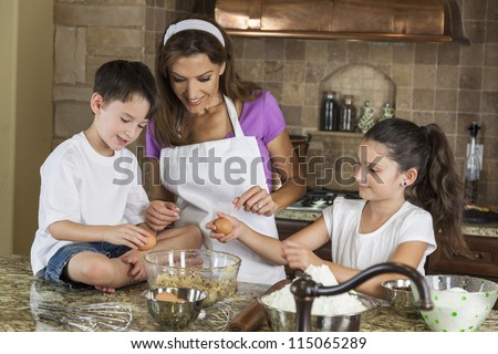 An attractive smiling family of mother, two children, girl, boy, son & daughter, breaking eggs & baking in a kitchen at home