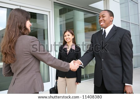 An attractive team of diverse business people shaking hands