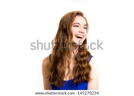 An attractive teen poses for a photo indoors in a lighting studio against a white background with a fashion style feel to the image. - Shutterstock ID 145270234