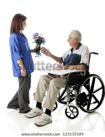 An attractive teen volunteer delivering a vase of flowers to an elderly man in a wheelchair.  On a white background.