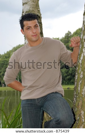 An attractive teenager on his lunch hour, taking a rest in the park. Photographed against a blue cloudy sky, leaning against a tree.