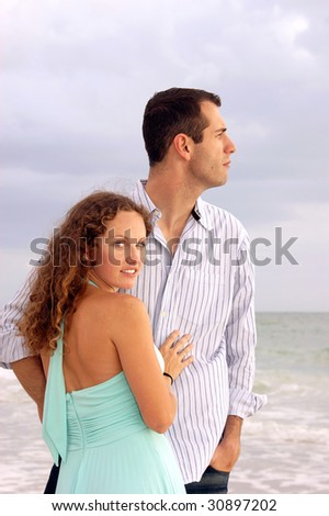 An attractive well dressed young couple  with their bodies facing each other, the man is looking out to the ocean in profile. The woman is turned and looking at viewer