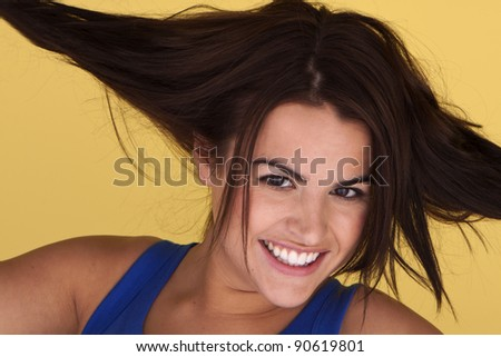 An attractive woman being happy with herself in playfully pulling her hair. Beautiful woman enjoying life.