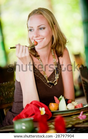 An attractive woman eating a healthy breakfast of fruit