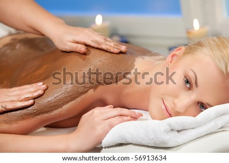 an attractive woman getting a chocolate massage at spa