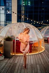 an attractive woman in a pink dress in a rooftop cafe. original and interesting place for dinner or date. femininity and cosmetics for women.