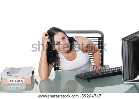 An attractive woman in a white tank-top, seated at a glass computer desk, appearing to be overwhelmed by her workload. There is an inbox full of invoices on the desk beside her.