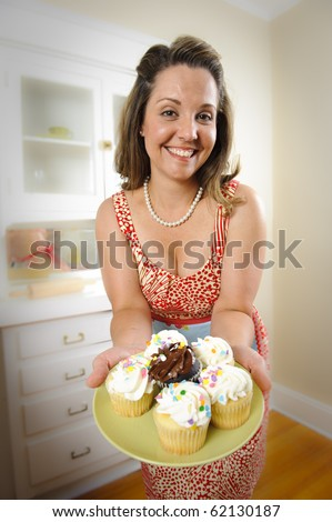 An attractive woman in vintage clothing offers cupcakes to her guests.