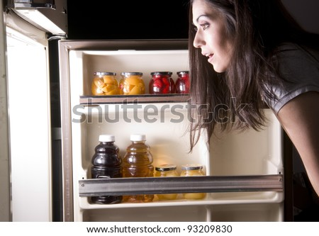 An attractive woman raids the refrigerator late at night looking for a food snack