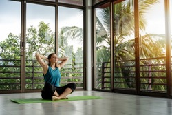 An attractive 40-year-old middle-aged woman practices yoga in a panoramic window room overlooking the garden at dawn in the sunshine. Meditation mindfulness healthy lifestyle concept.