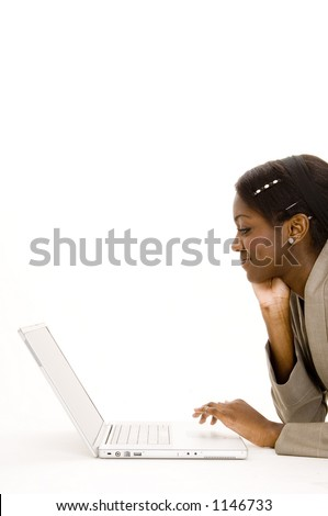 An attractive young black woman using a laptop computer on the floor - stock photo