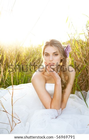 An attractive young bride wearing a white wedding dress and pearls is sitting with her head on her hand in the grass. Vertical shot.